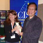 Liliane hands over the ICIS mascot and the Presidency to Vincent Chong